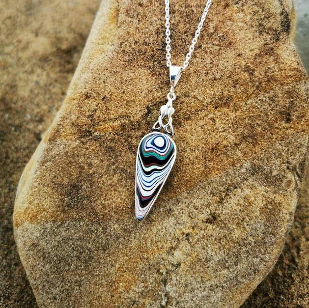 Fordite and Whitby Jet double sided inverse teardrop pendant.
